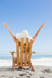 坐在轻便折叠躺椅的妇女在与胳膊的海滩 免版税库存照片