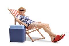 坐在轻便折叠躺椅的年长人在一个冷却的箱子旁边 免版税图库摄影