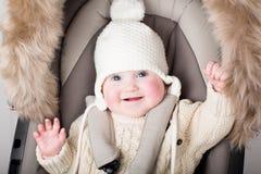 坐在婴儿推车的一个温暖的帽子的滑稽的婴孩 免版税库存照片