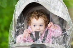 坐在婴儿推车的逗人喜爱的女婴在塑料雨下 免版税库存照片