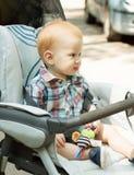 坐在婴儿推车的逗人喜爱的男婴 库存图片