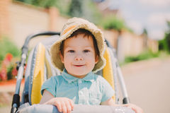 坐在婴儿推车的逗人喜爱的男婴 库存照片