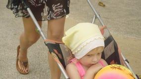 坐在婴儿车的逗人喜爱的小女孩 股票录像