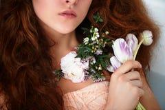 坐在浴和拿着花的美丽的浪漫红发女孩 一部分的面孔不是可看见的 在鞋带 免版税图库摄影