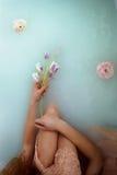 坐在浴和拿着花的美丽的浪漫红发女孩 面孔不是可看见的 在鞋带礼服 免版税库存照片