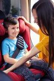 坐在婴孩的儿子好妈妈紧固安全带坐 库存图片