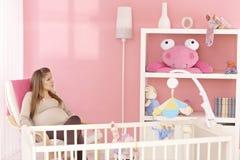 坐在婴孩的屋子里的怀孕的母亲 免版税库存照片