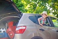 坐在离开之前的汽车的小孩男孩在假期 库存照片
