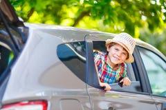 坐在离开之前的汽车的小孩男孩在假期 库存图片