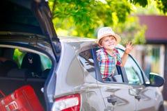 坐在离开之前的汽车的小孩男孩在假期 免版税库存照片