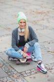 坐在滑板的时髦服装的妇女 库存照片