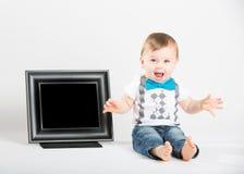 坐在画框和叫喊旁边的婴孩 免版税库存图片