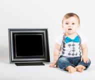坐在画框旁边和看照相机的婴孩 库存图片