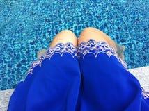 坐在水池旁边的一条蓝色裙子的妇女用清楚的水 免版税库存照片