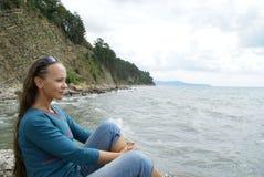 坐在黑海岸讨厌的天气的 免版税库存照片