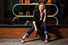 坐在购物中心窗口的年轻时髦的女人 免版税库存照片