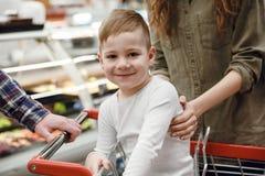坐在购物台车和看照相机的愉快的年轻男孩 库存图片