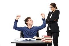 坐在他的书桌的学生愉快地看他的老师和 免版税库存图片