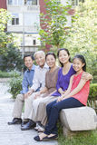 坐在他们的公寓庭院里的三一代家庭 免版税图库摄影