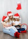 坐在他的圣诞老人帽子的母亲旁边的两个姐妹 免版税库存照片