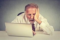 坐在他的在便携式计算机前面的书桌的疲乏的困老人 免版税库存图片
