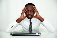 坐在他的工作场所的非洲商人 库存照片