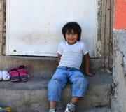坐在他的房子外面的墨西哥男孩 免版税图库摄影