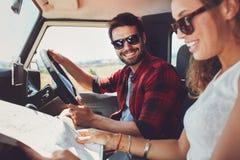 坐在他们的有地图的汽车里面的年轻夫妇 库存照片