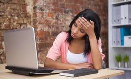 坐在他的有膝上型计算机的书桌的混乱的妇女 免版税库存照片
