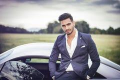 坐在他的汽车的英俊的年轻人 免版税库存照片