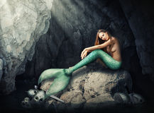 坐在洞的美丽的妇女美人鱼 免版税库存照片