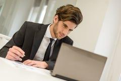 坐在他的膝上型计算机和工作在办公室的商人 库存图片