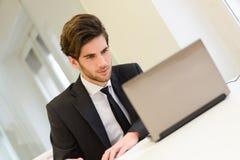 坐在他的膝上型计算机和工作在他的办公室的商人 免版税图库摄影