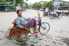 坐在他的trishaw的地方人在曼德勒, 2015年8月01日的缅甸镇  免版税库存图片