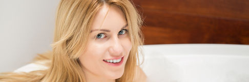 坐在浴缸的白肤金发的妇女 免版税库存图片