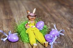 坐在绿色巢的黄色复活节陶瓷兔宝宝 免版税库存照片