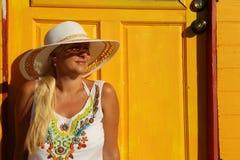 坐在黄色海滩小屋附近的女孩 免版税库存图片