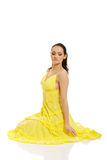 坐在黄色礼服的美丽的妇女 免版税库存图片
