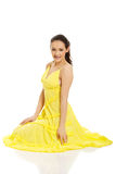 坐在黄色礼服的美丽的妇女 库存图片