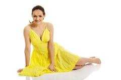 坐在黄色礼服的美丽的妇女 免版税库存照片