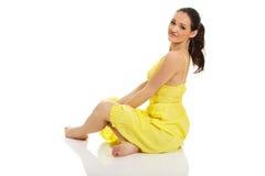 坐在黄色礼服的美丽的妇女 图库摄影