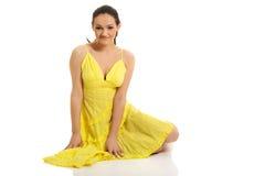 坐在黄色礼服的美丽的妇女 库存照片