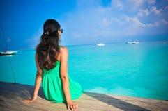 坐在绿色礼服的年轻亚裔看的妇女画象小屋在美丽的热带海滩在马尔代夫 免版税库存照片
