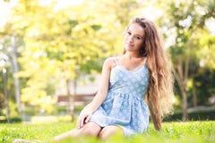 坐在绿草的美丽的少妇 免版税图库摄影