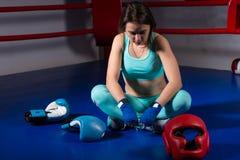 坐在说谎的拳击手套和盔甲附近的年轻女性拳击手 免版税库存照片