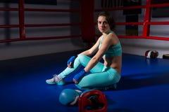 坐在说谎的拳击手套和盔甲附近的年轻运动妇女 图库摄影