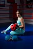 坐在说谎的拳击手套和盔甲附近的年轻运动的妇女 免版税库存图片