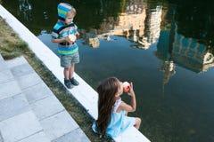 坐在水附近的小女孩和男孩 免版税库存照片