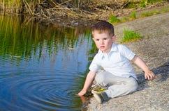 坐在水附近的男孩 免版税库存图片