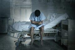 坐在医院病床哀伤和单独被毁坏的遭受的消沉的绝望人哭泣在诊所 免版税库存照片